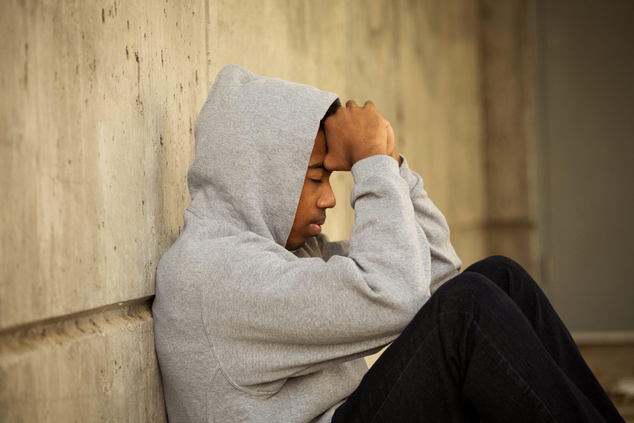 Man Sitting on Street Distressed