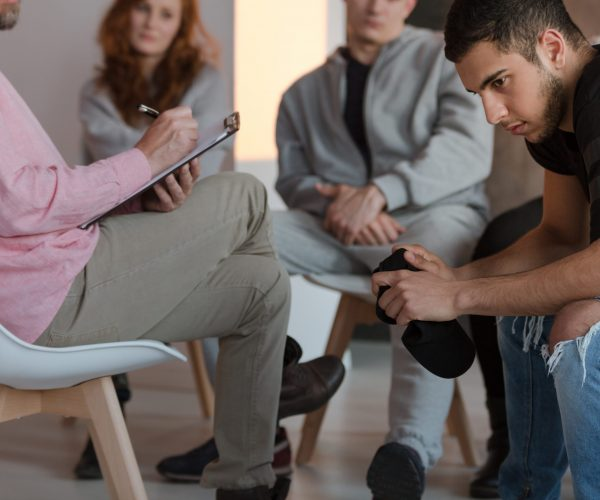 Arrogant,Teenager,Sitting,At,A,Meeting,Of,Support,Group,While