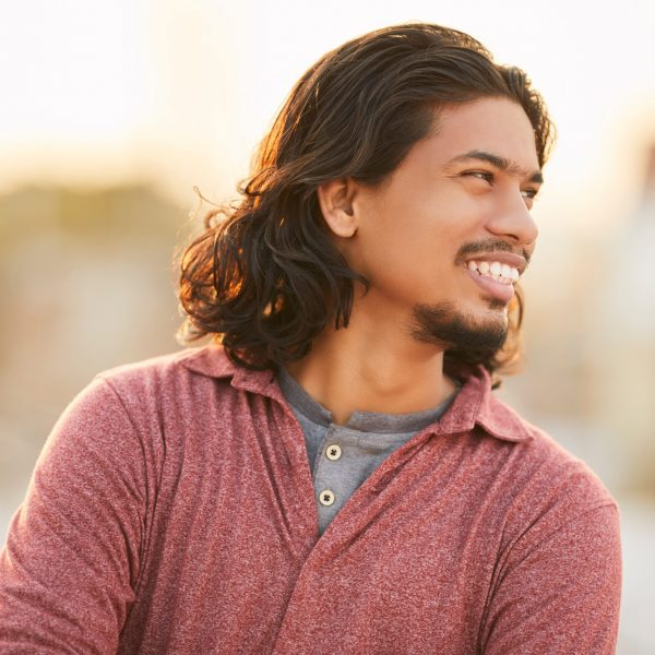 Cheerful,Indian,Young,Man,With,Long,Hair,At,Outdoor,Background.